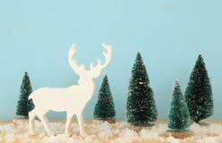 圣诞树和驯鹿的图象在多雪的木桌上 免版税库存图片