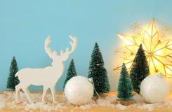 圣诞树和驯鹿的图象在多雪的木桌上 库存图片
