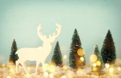 圣诞树和驯鹿的图象在多雪的木桌上 免版税图库摄影