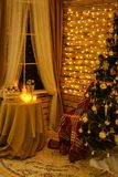 圣诞树在墙帷诗歌选的屋子,由窗口的一张桌里与蜡烛 图库摄影