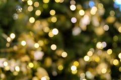 圣诞树在绿色黄色金黄颜色,假日抽象背景的bokeh光,弄脏defocused 免版税库存图片