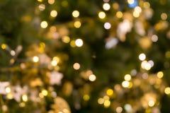 圣诞树在绿色黄色金黄颜色,假日抽象背景的bokeh光,弄脏defocused 免版税库存照片