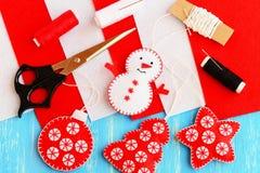圣诞树垂悬的装饰品 毛毡雪人、树、星和球装饰品,红色和白色螺纹,毛毡板料,剪刀,针 库存图片