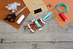 圣诞树姜饼人装饰,剪刀,螺纹,针,补白,毛毡覆盖,小珠,在老木桌上的按钮 免版税图库摄影