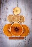 圣诞树形状由干桔子、柠檬和苹果制成在老木背景 库存图片