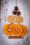 圣诞树形状由干桔子、柠檬和茴香制成在老木背景 免版税库存照片