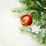圣诞树枝杈和红色球Xmas装饰在雪 免版税库存图片