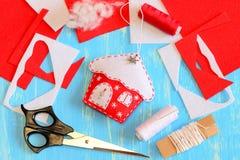 圣诞树用雪花和金属零件缝合从毛毡和装饰的房子装饰 工具和材料 免版税库存图片