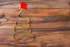 圣诞树由与一个红色星的绿色丝带制成在woode 免版税库存照片