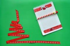 圣诞树由红色丝带,有把柄的笔记本制成以在绿色背景的一个雪人的形式 圣诞节和新年conce 免版税库存照片