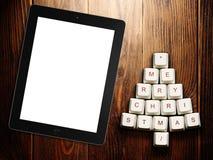 圣诞树由计算机键盘和片剂计算机制成在木背景 免版税库存图片