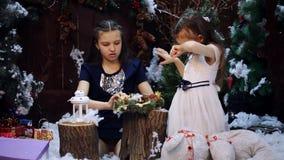 圣诞树的两女孩圣诞节花圈作为礼物为祖母做准备 股票录像
