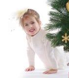 圣诞树的俏丽的女孩 免版税库存图片