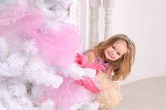 圣诞树的微笑的小女孩户内 免版税库存图片