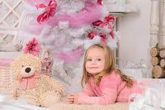 圣诞树的微笑的小女孩户内 免版税图库摄影