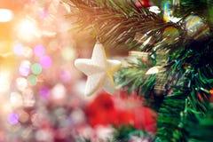 圣诞树的白色垂悬的星装饰品 发光的轻的与拷贝空间的火光快活的Xmas装饰背景为 库存图片