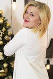 圣诞树背景的白肤金发的女孩  免版税库存图片