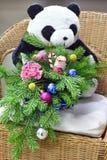 圣诞树花束与圣诞装饰和可爱的花的 在一把藤椅 玩具熊在背景中 免版税库存照片