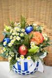 圣诞树花束与圣诞装饰和活玫瑰的 在一个镶边箱子的一把藤椅 免版税图库摄影