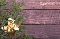 圣诞树装饰了红色弓、分支和锥体在木背景 库存照片