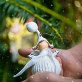 圣诞树装饰天使在小女孩的手上 库存照片