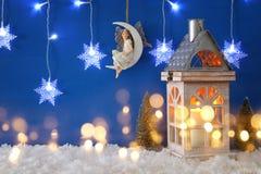 圣诞树,老灯笼,雪花变成银色诗歌选光、神仙月亮的在雪和蓝色背景 库存图片