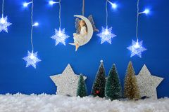 圣诞树,雪花变成银色诗歌选光、神仙月亮的在雪和蓝色背景 图库摄影