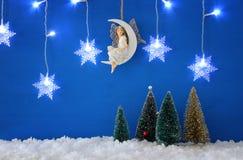 圣诞树,雪花变成银色诗歌选光、神仙月亮的在雪和蓝色背景 库存照片