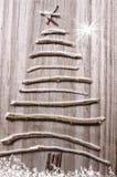 圣诞树从在木多雪的灰色背景的棍子安排了 图库摄影