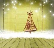 圣诞树从在空的木甲板桌上的棍子安排了在闪耀的绿色背景 为产品显示蒙太奇准备 免版税图库摄影