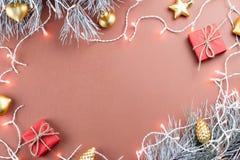 圣诞灯、金黄装饰品、红色giftbox和冷杉分支在棕色背景 库存照片