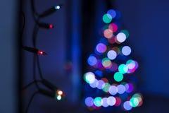 圣诞灯串垂悬在墙壁上的,有defocused xmas树的在背景中 圣诞灯bokeh 免版税图库摄影