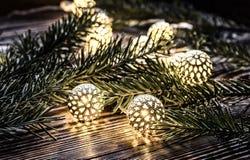 圣诞灯和冷杉分支在木背景 葡萄酒诗歌选和bokeh 免版税库存图片