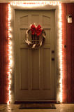 圣诞灯和花圈在前门在晚上 免版税库存图片