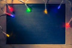 圣诞灯小条在小黑板顶部的 库存图片
