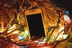 圣诞灯o和智能手机 库存图片