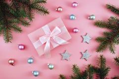 圣诞礼物,被编织的毯子,杉木锥体,在桃红色背景的冷杉分支 平的位置,顶视图,拷贝空间 库存图片