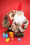 圣诞老人、酒瓶、pincone和五颜六色的圣诞节礼物bo 库存图片