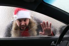 圣诞老人一个红色盖帽的人一辆汽车的有残破的玻璃的 库存照片