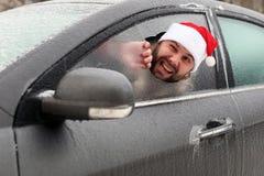 圣诞老人一个红色盖帽的人一辆汽车的有残破的玻璃的 免版税图库摄影