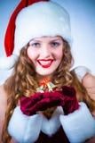 圣诞老人一个红色礼服和帽子的妇女与圣诞节的 免版税图库摄影