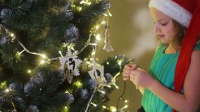 圣诞老人一个绿色礼服和帽子的愉快的女孩少年女小学生装饰一棵大圣诞树 圣诞节传统 股票视频