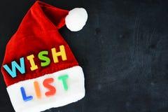 圣诞老人与五颜六色的文本的愿望概念在Santa's红色帽子 图库摄影