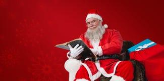 圣诞老人与大袋的读书圣经的综合图象在他旁边的圣诞节礼物 免版税图库摄影