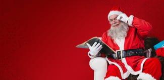 圣诞老人与大袋的读书圣经的综合图象在他旁边的圣诞节礼物 免版税库存图片