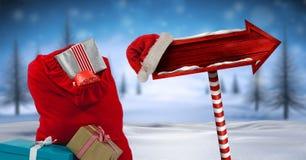 圣诞老人与礼物和木路标的` s袋子在圣诞节冬天风景和圣诞老人帽子 免版税图库摄影