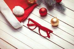 圣诞老人与红色玻璃的帽子和圣诞节泡影 图库摄影