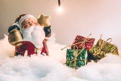 圣诞老人举行响铃和星和电灯泡在沈默夜站立,打开充满希望的人和幸福在圣诞快乐 免版税库存照片
