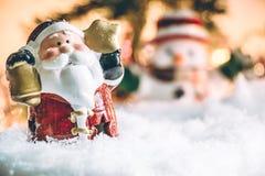 圣诞老人举行响铃和星在雪站立 图库摄影