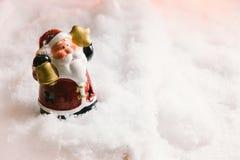 圣诞老人举行响铃和星在雪站立 免版税图库摄影